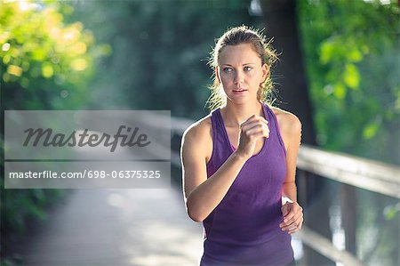 Healthy female jogging down track Stock Photo - Premium Royalty-Free, Image code: 698-06375325