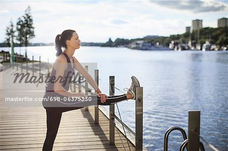 Side view of young woman stretching leg on fence
