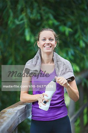 Portrait of smiling young woman holding water bottle Stock Photo - Premium Royalty-Free, Image code: 698-06375336