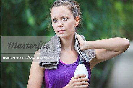 Tired young woman holding water bottle with towel around neck Stock Photo - Premium Royalty-Free, Image code: 698-06375338