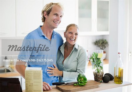 Happy couple embracing in kitchen Stock Photo - Premium Royalty-Free, Image code: 698-06375345