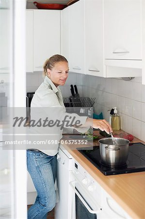 Mid adult woman cooking in kitchen Stock Photo - Premium Royalty-Free, Image code: 698-06375352