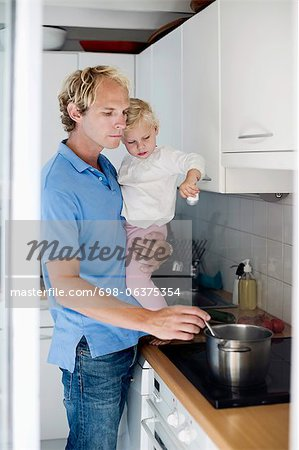 Man preparing food while holding daughter in kitchen Stock Photo - Premium Royalty-Free, Image code: 698-06375354