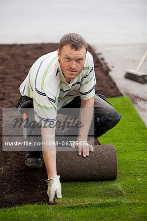 Portrait of a mid adult man rolling new grass turf in lawn Stock Photo - Premium Royalty-Free, Image code: 698-06375476