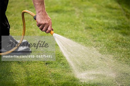 Cropped image of man watering grass turf in lawn Stock Photo - Premium Royalty-Free, Image code: 698-06375481
