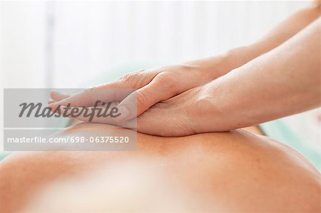 Close-up of human hand giving a back massage at beauty spa Stock Photo - Premium Royalty-Free, Image code: 698-06375520