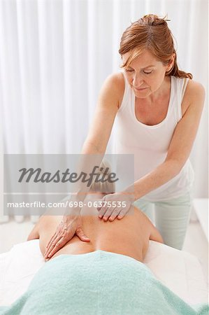 Mature masseur giving a back massage to female customer at health spa Stock Photo - Premium Royalty-Free, Image code: 698-06375535