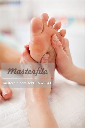 Human hand massaging sole of foot at health spa Stock Photo - Premium Royalty-Free, Image code: 698-06375541