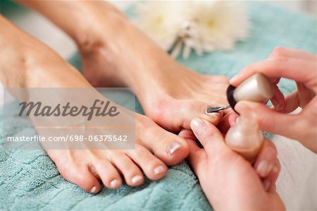 Close-up of a female feet receiving a beauty treatment for nails in spa Stock Photo - Premium Royalty-Free, Image code: 698-06375542
