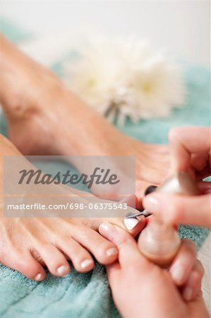 Close-up of a beautician applying nail polish on female customer's toenail in beauty spa Stock Photo - Premium Royalty-Free, Image code: 698-06375543