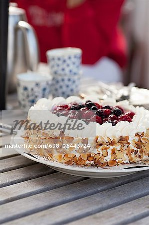 Fresh cake with berry fruit topping served in plate on wooden table Stock Photo - Premium Royalty-Free, Image code: 698-06443724
