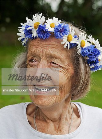 Close-up of happy senior woman with wreath of flowers on her head Stock Photo - Premium Royalty-Free, Image code: 698-06443896