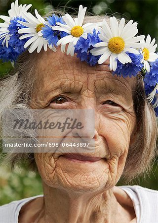 Portrait of senior woman wearing wreath of flowers on her head Stock Photo - Premium Royalty-Free, Image code: 698-06443897