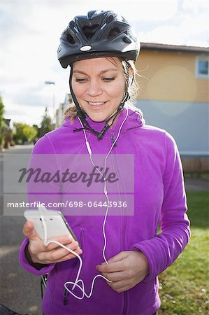 Happy woman in cycling helmet listening to music through cell phone Stock Photo - Premium Royalty-Free, Image code: 698-06443936