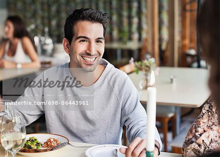 Happy man looking at female friend at restaurant table with people in the background Stock Photo - Premium Royalty-Free, Image code: 698-06443961