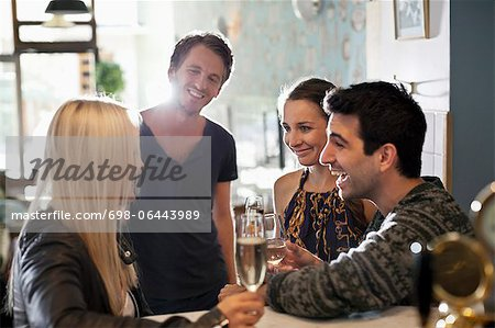 Group of happy friends holding wine glasses in saloon Stock Photo - Premium Royalty-Free, Image code: 698-06443989