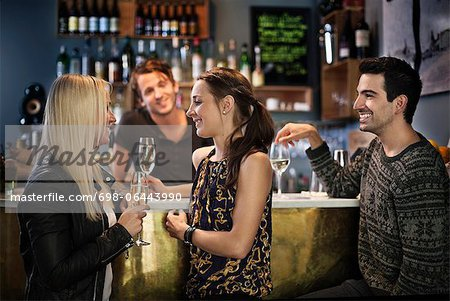 Side view of friends smiling while bar tender looking at them Stock Photo - Premium Royalty-Free, Image code: 698-06443990