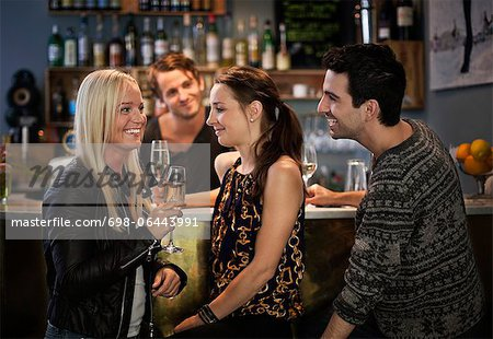 Bar tender looking at friends smiling at counter Stock Photo - Premium Royalty-Free, Image code: 698-06443991