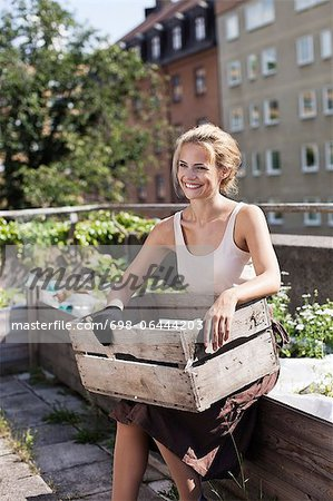 Happy young woman with wooden crate sitting at urban garden Stock Photo - Premium Royalty-Free, Image code: 698-06444203