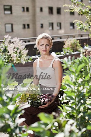 Portrait of young woman sitting at urban garden Stock Photo - Premium Royalty-Free, Image code: 698-06444208