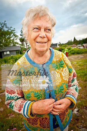 Happy senior woman standing at park looking away Stock Photo - Premium Royalty-Free, Image code: 698-06444276