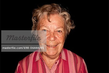 Portrait of happy senior woman against black background Stock Photo - Premium Royalty-Free, Image code: 698-06444281