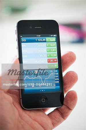 Man's hand showing business graph on smart phone Stock Photo - Premium Royalty-Free, Image code: 698-06444391