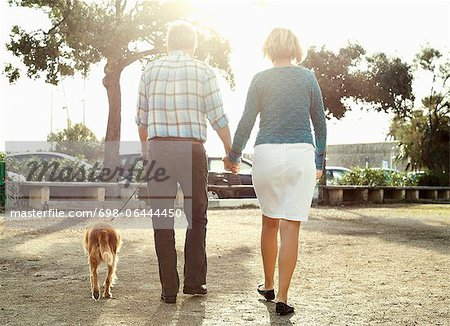 Rear view of couple walking with dog in park Stock Photo - Premium Royalty-Free, Image code: 698-06444450