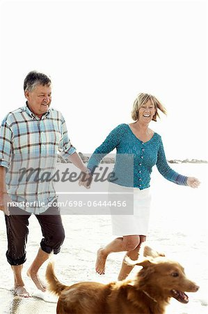 Happy couple running behind dog at beach Stock Photo - Premium Royalty-Free, Image code: 698-06444456