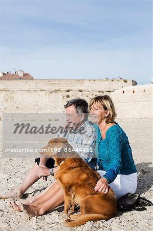 Couple with dog sitting on sand at beach Stock Photo - Premium Royalty-Free, Image code: 698-06444461