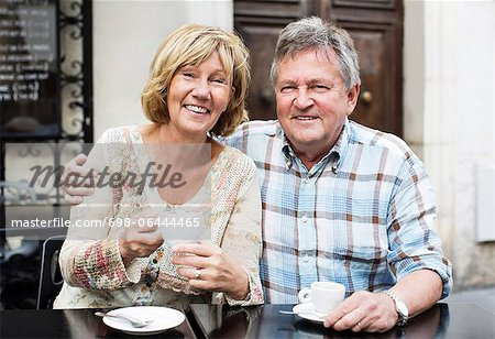 Portrait of happy couple having coffee at table Stock Photo - Premium Royalty-Free, Image code: 698-06444465
