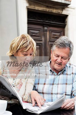 Happy couple reading newspaper at restaurant table Stock Photo - Premium Royalty-Free, Image code: 698-06444471