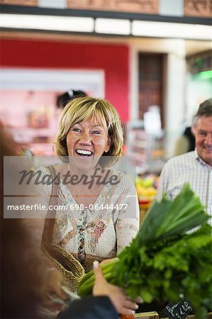 Woman buying vegetables at market Stock Photo - Premium Royalty-Free, Image code: 698-06444477