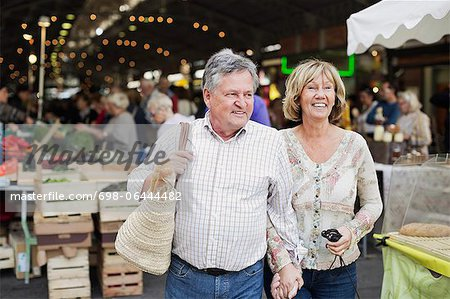 Happy couple looking away with market in the background Stock Photo - Premium Royalty-Free, Image code: 698-06444482