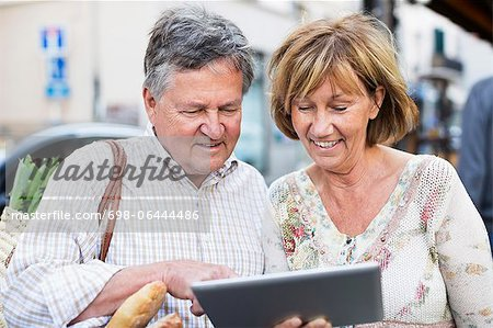 Happy couple using digital tablet Stock Photo - Premium Royalty-Free, Image code: 698-06444486