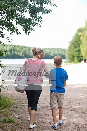 Rear view of mature woman with son walking on beach during vacations Stock Photo - Premium Royalty-Free, Image code: 698-06444506