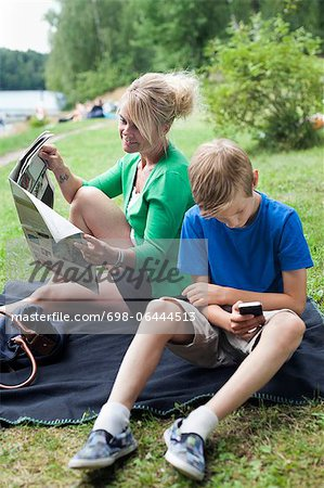 Mature woman reading newspaper sitting with son using cell phone at park Stock Photo - Premium Royalty-Free, Image code: 698-06444513