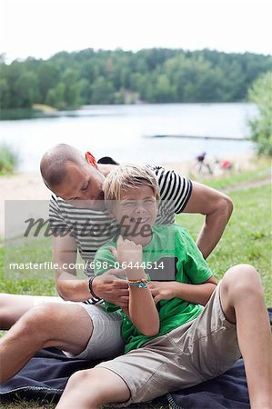 Playful pre-adolescent child with father sitting at park Stock Photo - Premium Royalty-Free, Image code: 698-06444514