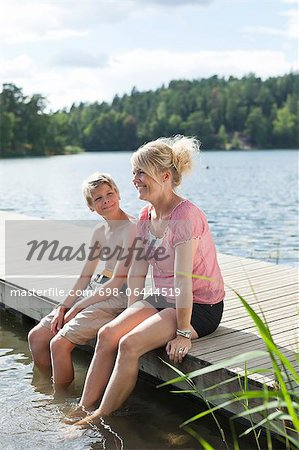 Happy mature woman sitting with son on pier during vacations Stock Photo - Premium Royalty-Free, Image code: 698-06444519