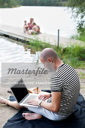 Mature man using laptop at beach with family sitting on pier Stock Photo - Premium Royalty-Free, Image code: 698-06444524