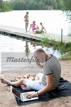 Mature man using laptop while communicating on cell phone at beach with family sitting on pier Stock Photo - Premium Royalty-Free, Image code: 698-06444526
