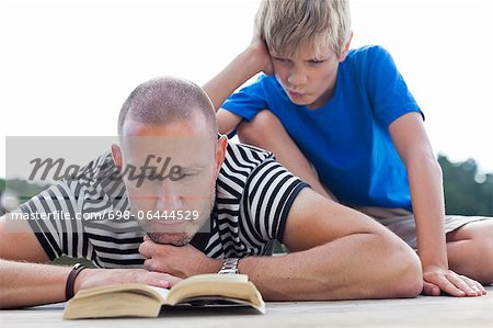 Mature man reading book while lying on pier with son sitting behind Stock Photo - Premium Royalty-Free, Image code: 698-06444529