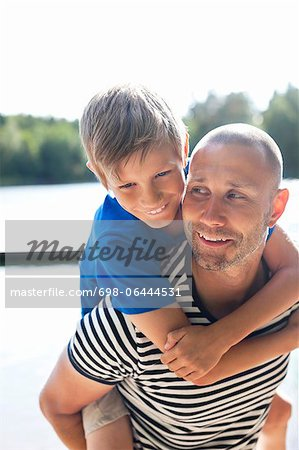 Happy mature man giving his son a piggyback ride at beach Stock Photo - Premium Royalty-Free, Image code: 698-06444531