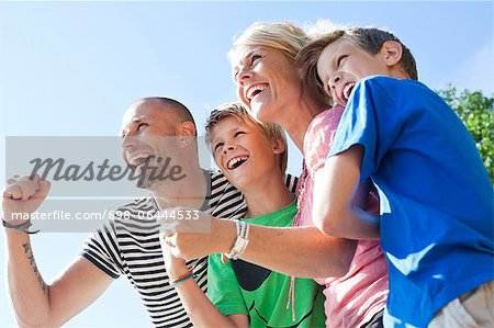 Low angle view of happy Caucasian family enjoying together against clear sky Stock Photo - Premium Royalty-Free, Image code: 698-06444533