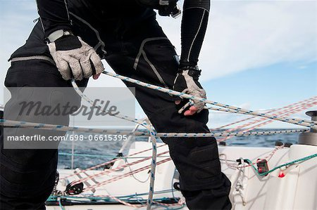 Midsection of man tying rope of sailboat Stock Photo - Premium Royalty-Free, Image code: 698-06615395