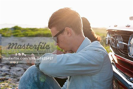 Side view of young man with woman sitting in front of car Stock Photo - Premium Royalty-Free, Image code: 698-06615487