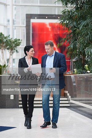 Full length of businessman with female colleague discussing paperwork while walking in office Stock Photo - Premium Royalty-Free, Image code: 698-06615513