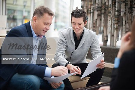 Happy businessmen going through paperwork in office Stock Photo - Premium Royalty-Free, Image code: 698-06615514