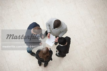 Directly above shot of four businesspeople in meeting Stock Photo - Premium Royalty-Free, Image code: 698-06615519