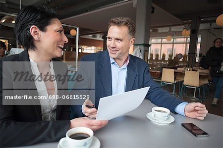 Mature businessman with female colleague discussing paperwork in cafe Stock Photo - Premium Royalty-Free, Image code: 698-06615529